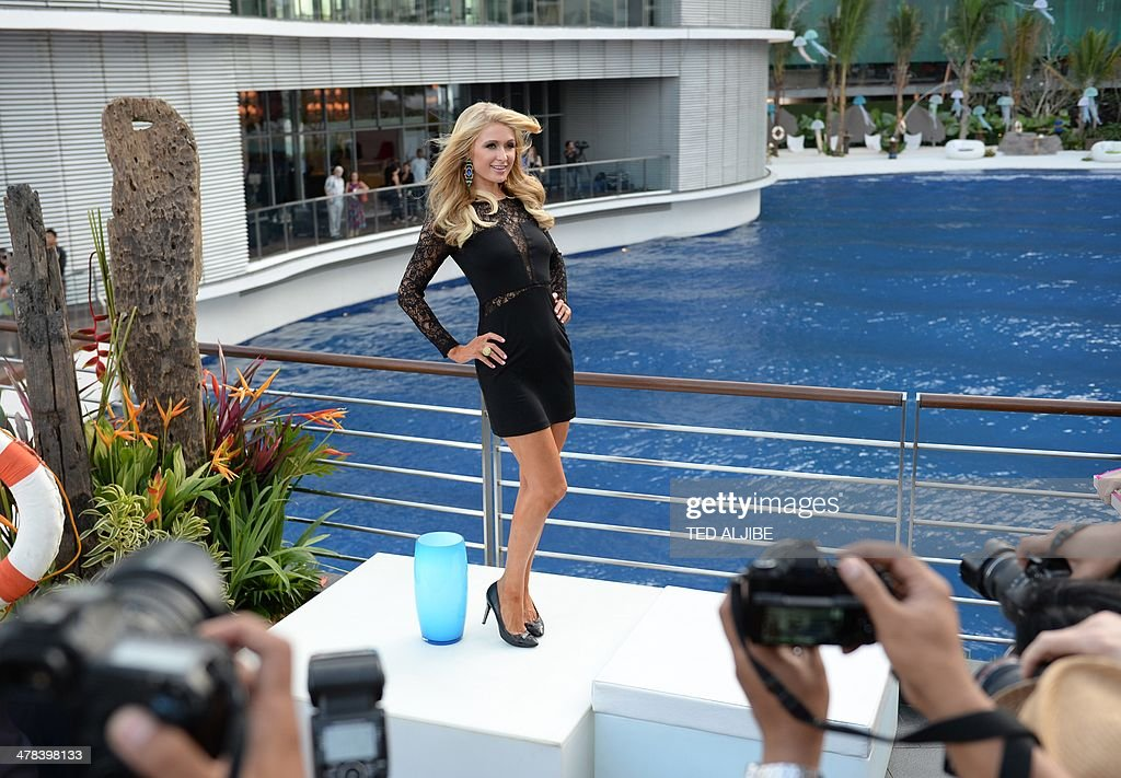 US socialite and entertainer Paris Hilton poses for photographers during the inauguration of her first real estate project, the Paris Beach Club, in Manila on March 13, 2014. Hilton unveiled the Paris Beach Club in collaboration with Century Properties, a high-end real estate developer in the country's capital. AFP PHOTO/TED ALJIBE