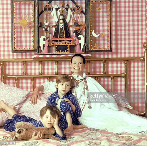 Socialite and heiress Gloria Vanderbilt poses for a portrait session with her sons Anderson Cooper and Carter Vanderbilt Cooper on a bed in their...