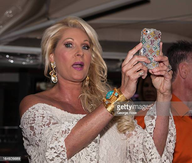 A socialite attending a rooftop pool party and wine tasting at the Joule Hotel takes pictures with her iPhone on March 20 2013 in Dallas Texas Dallas...