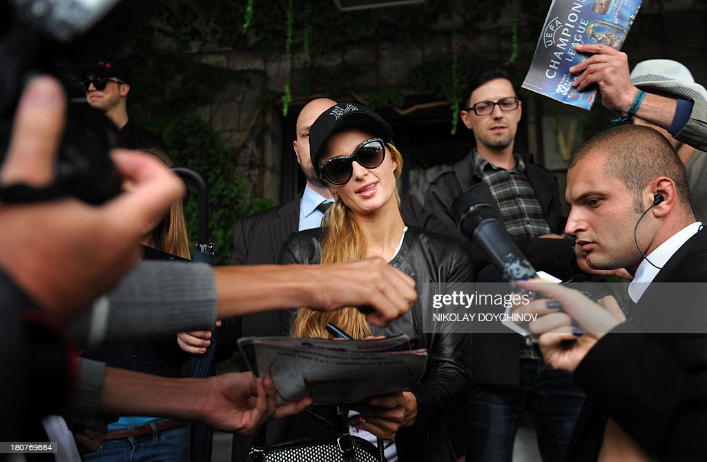 US socialite Paris Hilton gives autographs as she arrives at Sofia Airport on September 16, 2013. Hilton will participate inthe Bulgarian VIP brother reality show this week.