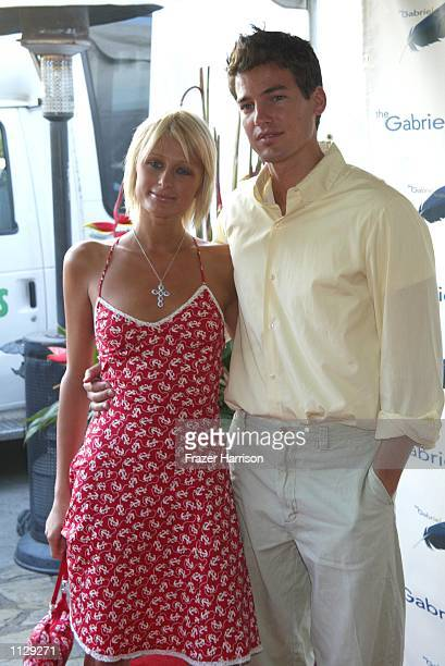 Socialite Paris Hilton with friend Jason Shaw attends the Parrots in Paradise benefit at the Playboy Mansion June 27 2002 in Beverly Hills California...