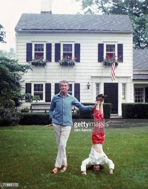 Society photographer Slim Aarons helps his daughter Mary to sustain a headstand Bedford New York 4th July 1970