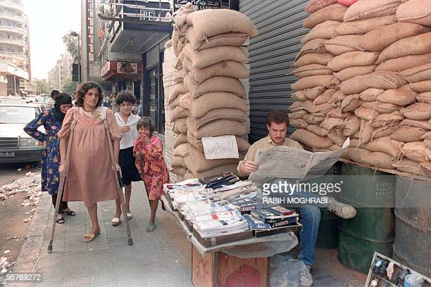 A socks street merchant reads his newspaper 18 August 1989 in Muslim West Beirut while a crippled woman passes across with her similar daughter in...