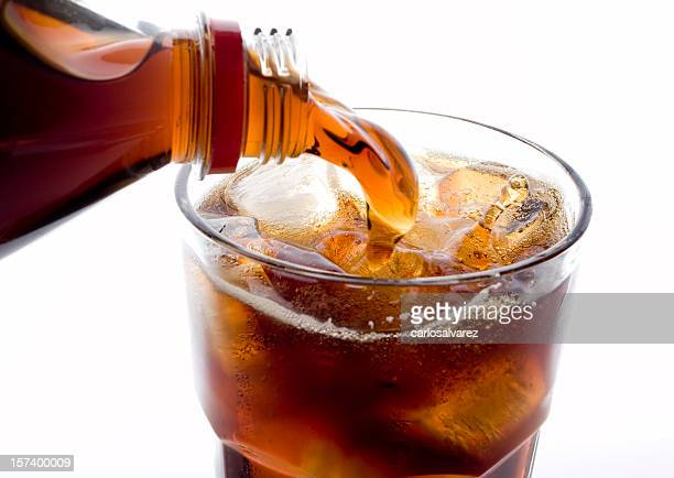 Soda (cola) being poured into plain glass with ice