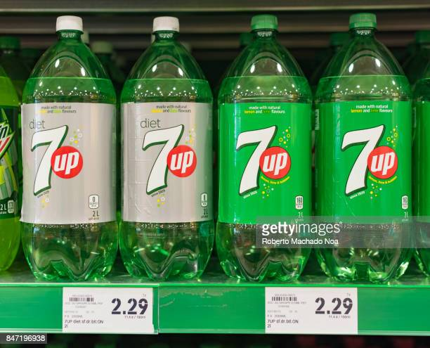 UP soda bottles on display with price tags below diet and normal bottles arranged neatly on a grocery store shelf