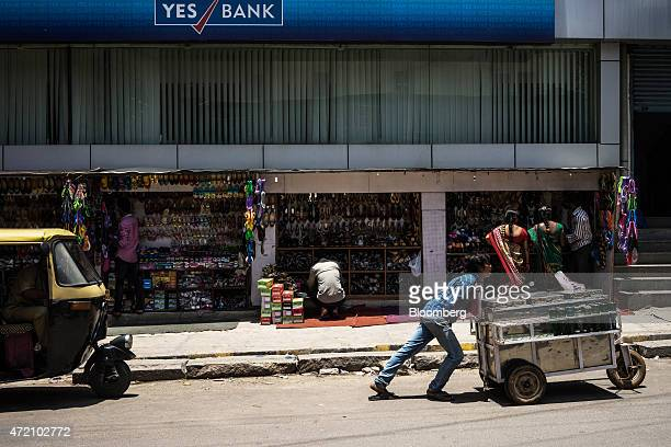 A soda vendor pushes a cart past footwear stalls and a branch of Yes Bank Ltd in the Malleswaram district of Bangalore India on Sunday May 3 2015...