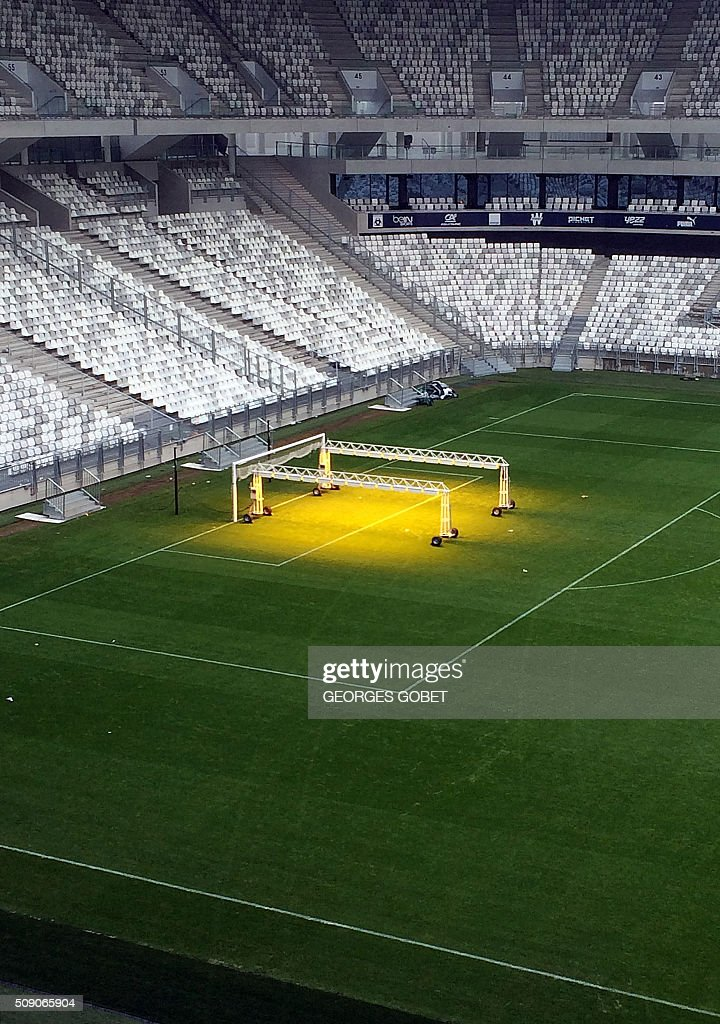 Sodium lights are used to improve the quality of the grass of a football field at the Matmut-Atlantique stadium in Bordeaux, southwestern France, on February 8, 2016 as part of the preparation of the Euro 2016 tournament. / AFP / GEORGES GOBET