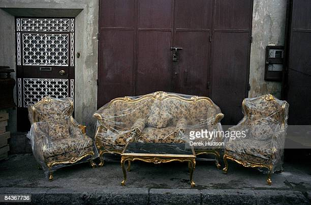A sofa and two chair set with coffee table in mock French period style complete with guilt trimmings with protective plastic coverings on a sidewalk...