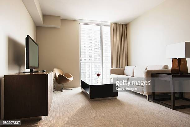 Sofa, coffee table and television in modern hotel room