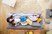 A mother is lying on the sofa in the living room of her home, with her son and daughter. The girl is lying on the other end of the sofa and is laughing while looking at the camera.