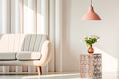 White, elegant sofa, pink lamp and flowers on metal table in a living room interior