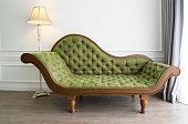 A tufted green chaise longue with a solid wood frame sitting on a wood floor.  On the right of the chaise lounge is a lighted white floor lamp.