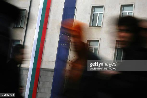 Bulgarians pass giant Bulgarian and European Union flags stretched on a building in downtown Sofia 18 December 2006 two weeks before the official...