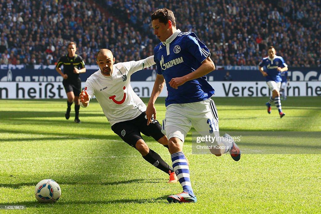 Sofian Chahed of Hannover challenges Julian Draxler of Schalke during the Bundesliga match between FC Schalke 04 and Hanover 96 at Veltins Arena on...