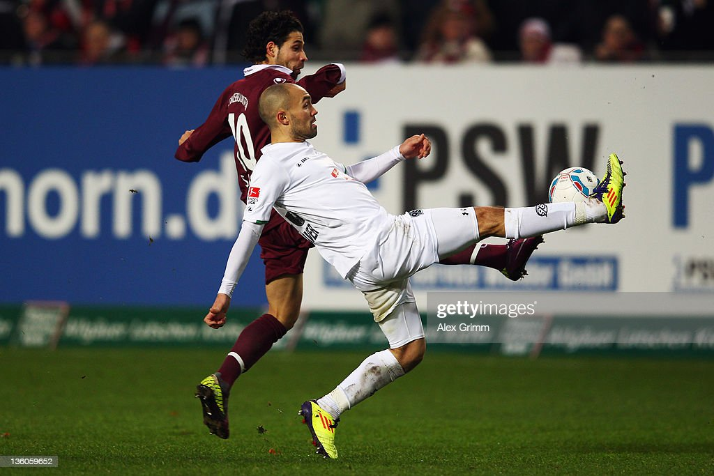 Sofian Chahed of Hannover is challenged by Olcay Sahan of Kaiserslautern during the Bundesliga match between 1 FC Kaiserslautern and Hannover 96 at...