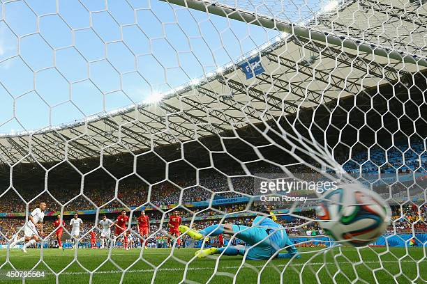 Sofiane Feghouli of Algeria celebrates scoring his team's first goal on a penalty kick past Thibaut Courtois of Belgium during the 2014 FIFA World...