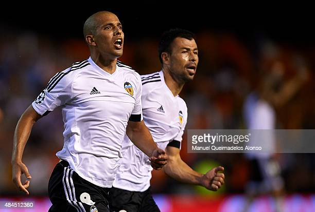 Sofiane Feghouli of Valencia celebrates scoring his team's third goal with his teammate Javi Fuego during the UEFA Champions League Qualifying Round...