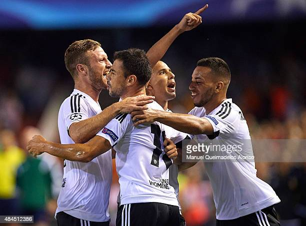 Sofiane Feghouli of Valencia celebrates scoring his team's third goal with teammates during the UEFA Champions League Qualifying Round Play Off First...