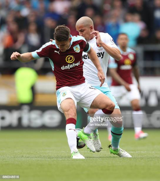 Sofiane Feghouli of West Ham United vies with Ashley Westwood of Burnley during the Premier League match between Burnley and West Ham United at Turf...