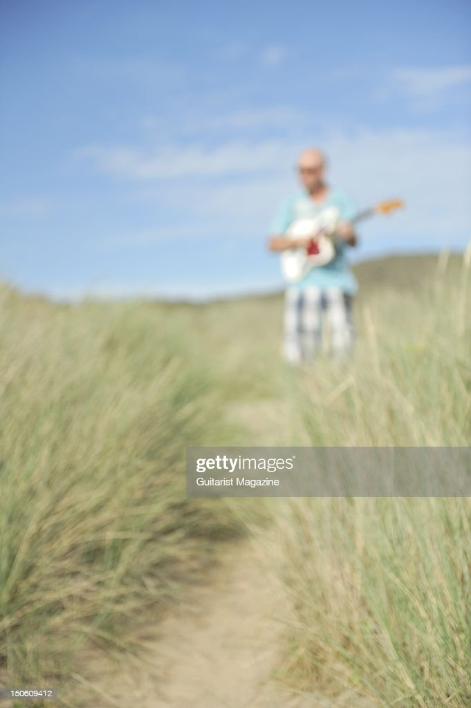 Soft focus picture of a man on a beach playing a Fender Jaguar electric guitar, session for Guitarist Magazine taken on July 1, 2011.