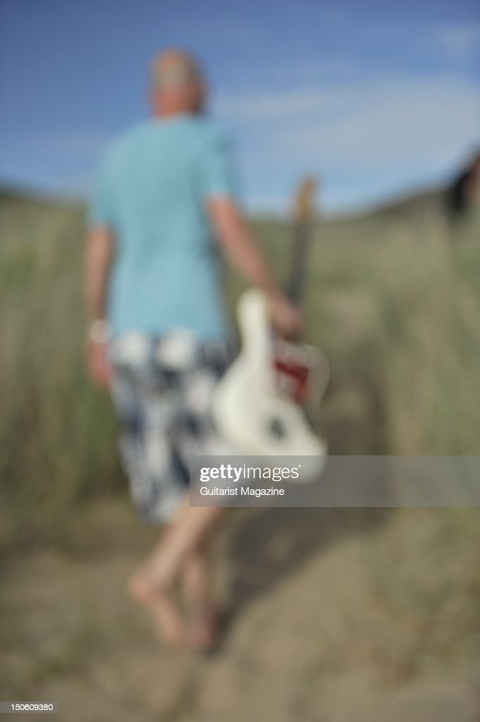 Soft focus picture of a man walking on a beach carrying a Fender Jaguar electric guitar, session for Guitarist Magazine taken on July 1, 2011.