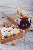 Soft french cheese of camembert served with chopped walnuts, glass of red wine and blueberries on wooden plate.