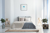 Knitted blanket on king-size bed in natural warm bedroom of modern apartment in soft gray and blue colors