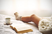 Soft photo of woman on the bed with old book and cup of coffee