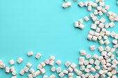 Soft pink and white marshmallows on light blue background. Flat lay, top view. gentle background  with candies with copy space.