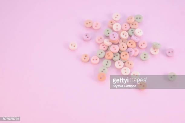 Soft pink, orange and green buttons on pink paper background