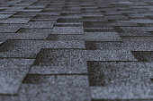 Soft roof tiled gray grainy texture on the top of a village house; grey soft roofing tiles covering a building, focus on the middle distance, shallow depth of field