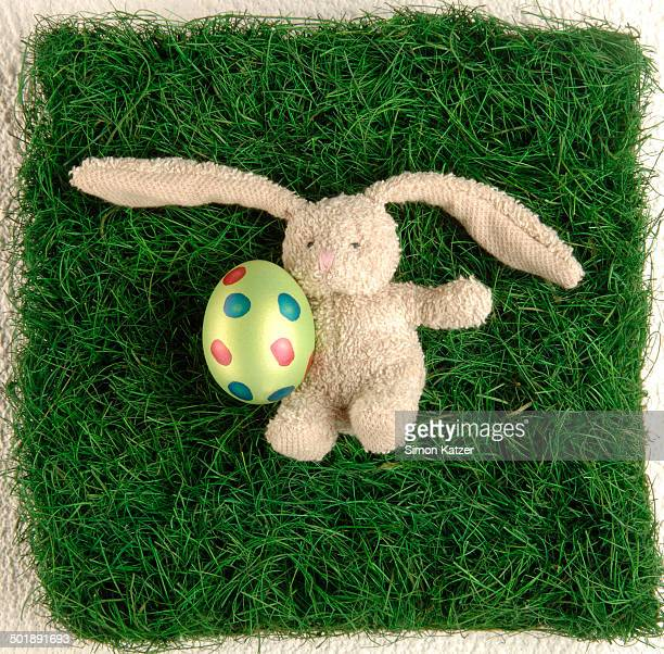 Soft toy, bunny, holding an Easter egg, lying in a meadow