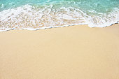 Soft wave of blue ocean on golden sandy beach. Background.