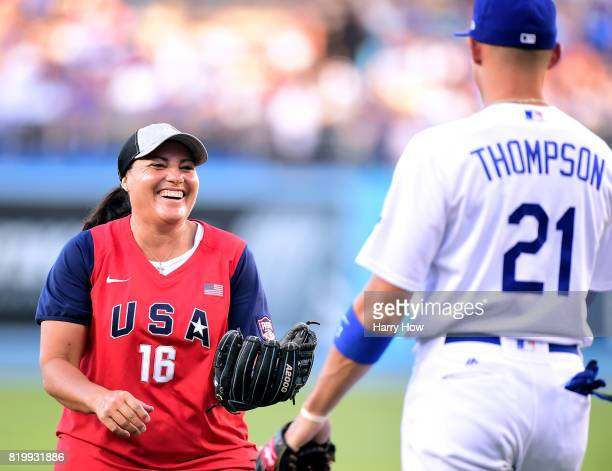 Softball Olympian Lisa Hernandez laughs with Trayce Thompson of the Los Angeles Dodgers after throwing out a ceremonial first pitch before the game...