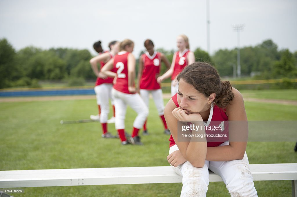 Softball Player Sitting on Bench with head down : Stock Photo