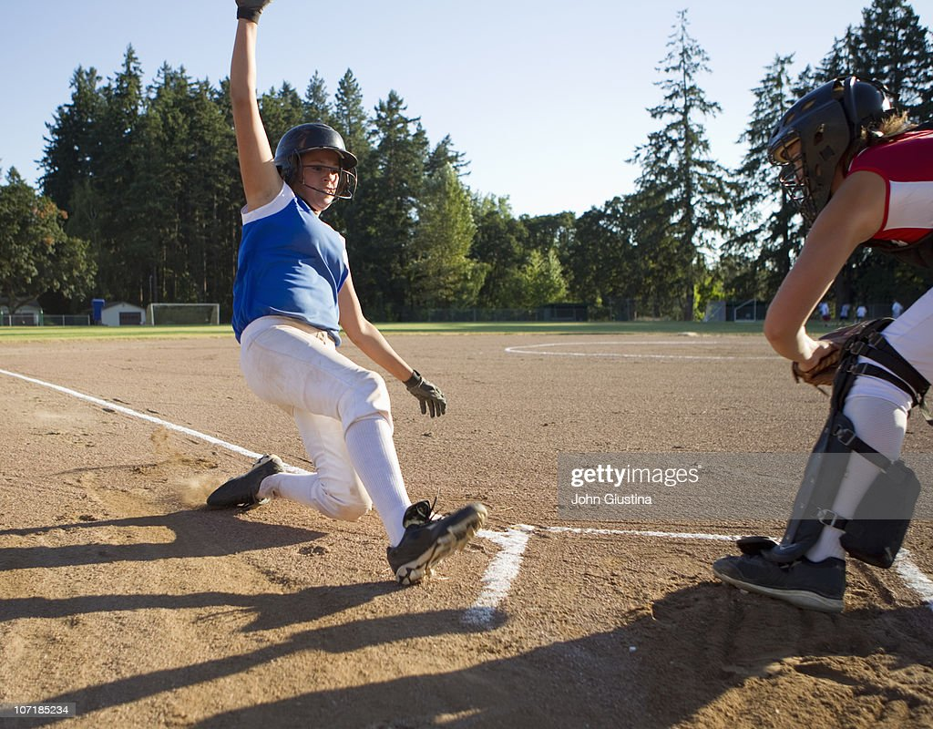 Softball player slides at home plate. : Stock Photo