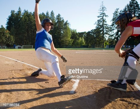 Softball player slides at home plate. : ストックフォト