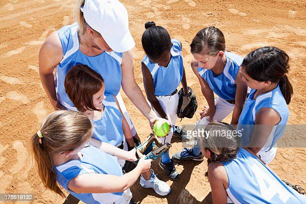 Softball team with coach in huddle