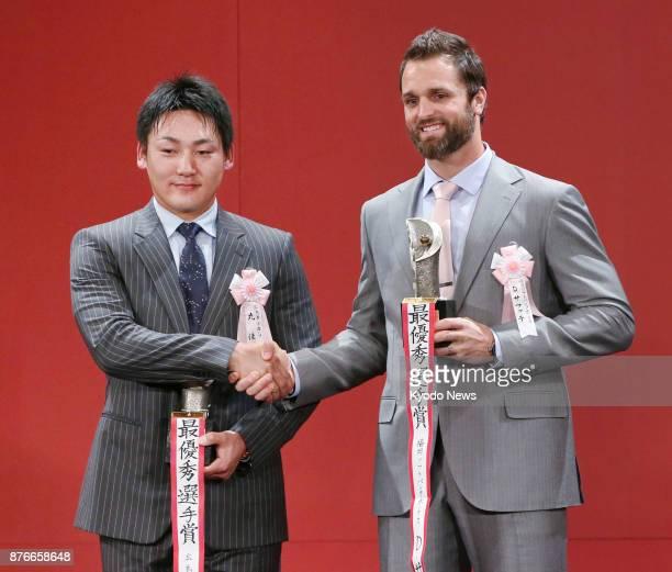 SoftBank Hawks closer Dennis Sarfate and Hiroshima Carp outfielder Yoshihiro Maru shake hands at a Tokyo hotel on Nov 20 after they were named Nippon...