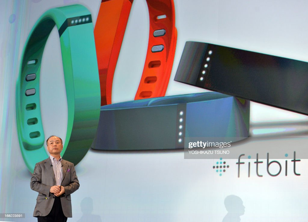 Softbank president Masayoshi Son announces the launch of the new health care service using wristband styled devices 'Fitbit Flex' and smartphones in Tokyo on May 7, 2013. The Fitbit Flex monitors data through a pedometer, calorie consumption and hours of sleep and transfers the information to a smartphone to maintain the user's health. Softbank is expecting to start the service from this summer. AFP PHOTO / Yoshikazu TSUNO