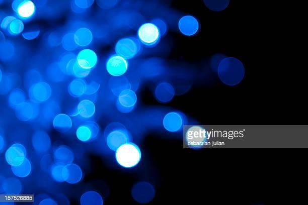 Soft-focus twinkling blue lights on black