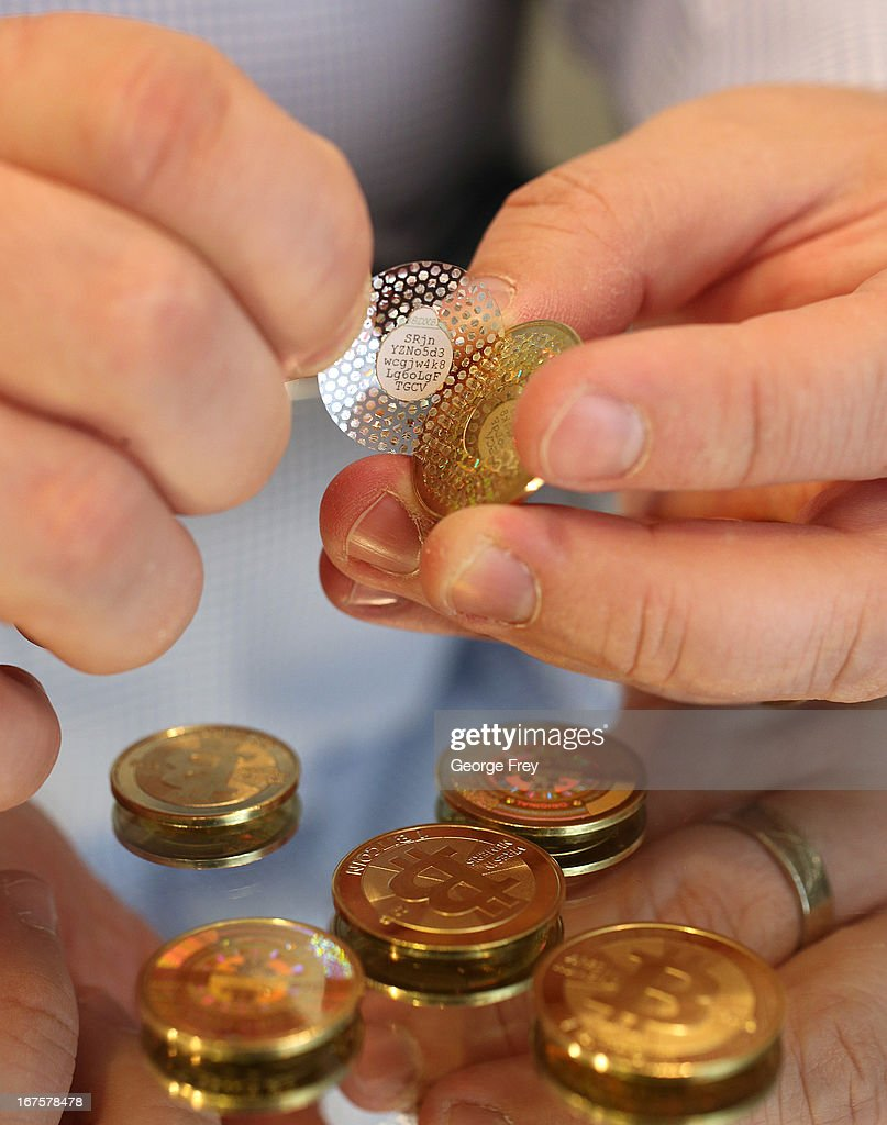 Software engineer Mike Caldwell peels back the hologram of a new Bitcoin he minted to reveal a code in his shop on April 26, 2013 in Sandy, Utah. Bitcoin is an experimental digital currency used over the Internet that is gaining in popularity worldwide.