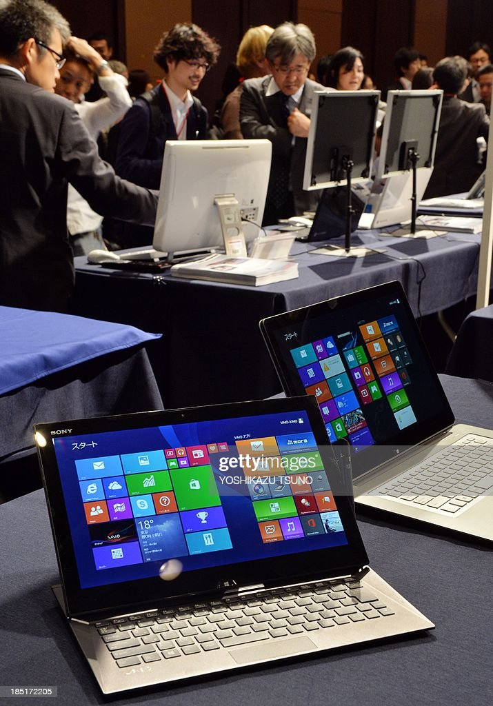 US software giant Microsoft pre-installed Windows 8.1 personal computers and tablets are displayed at a Windows 8.1 launching event in Tokyo on October 18, 2013. Microsoft released Windows 8.1 worldwide on October 18, after tweaking the operating system designed for various devices that had confused some users. The revamped version brings back the 'start' button, which disappeared last year and prompted protests from some PC users unaccustomed to the tiled menu adapted for touchscreens. AFP PHOTO / Yoshikazu TSUNO