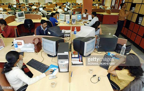 Software Professionals of Indian software firm Ivega Corp work at their workstations at the company's office in Global Village in India's technology...