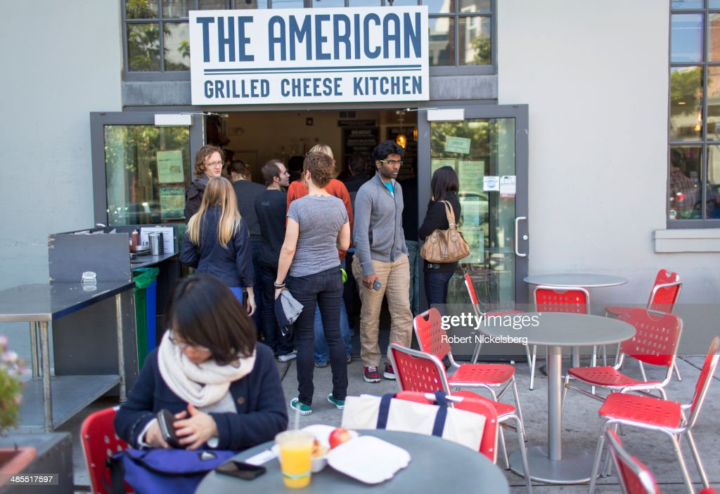 Software technology employees line up at a restaurant April 14, 2014 near South Park's start-up district in San Francisco, California.