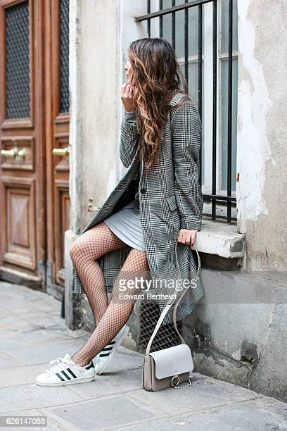 Sofya Benzakour is wearing a Tobi dress an HM black and white coat Adidas shoes and a Nakd Fashion gray bag on November 27 2016 in Paris France