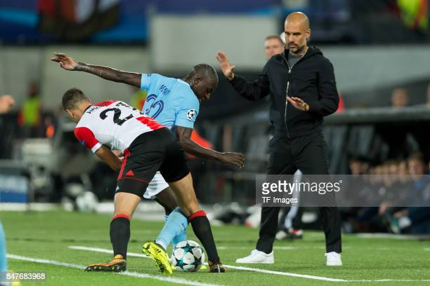 Sofyan Amrabat of Rotterdam and Benjamin Mendy of Manchester City battle for the ball Head coach Pep Guardiola of Manchester City during the UEFA...