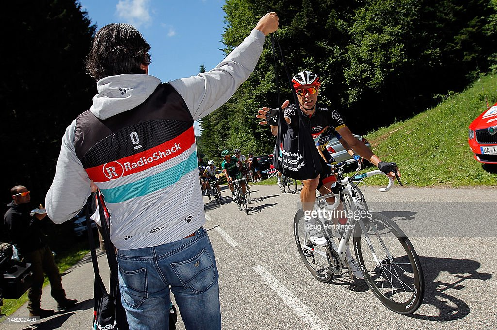 Soigneur Elvio Barcella of Radioshack-Nissan delivers a musette bag to Jens Voigt of Germany riding for Radioshack-Nissan in the feed zone during stage ten of the 2012 Tour de France from Macon to Bellegarde-Sur-Valserine on July 11, 2012 in Bellegarde-sur-Valserine, France.
