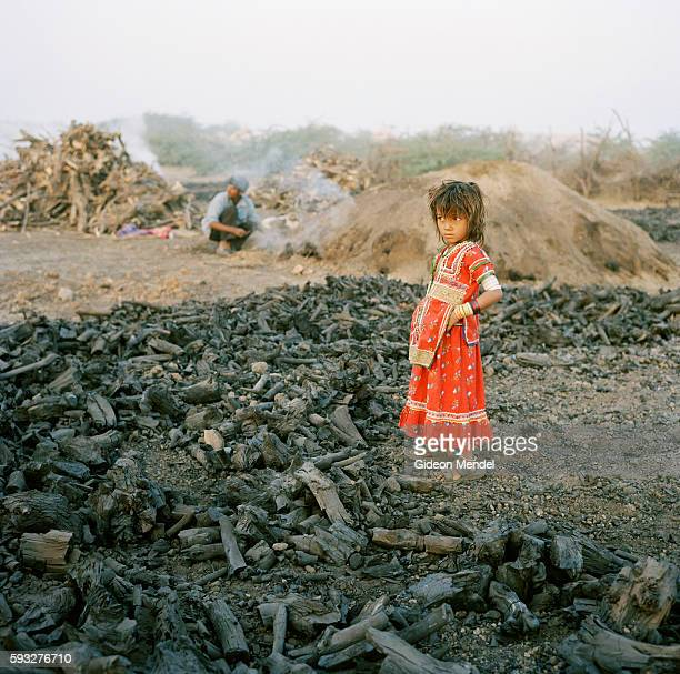 Soji Raja Harijan plays amidst a pile of charcoal produced by her uncles charcoal burners in Harijan Vaasone of the hamlets that make up the Hodka...