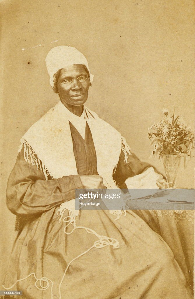 Sojourner Truth, three-quarter length portrait, seated at table with knitting and book